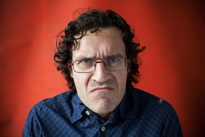 Man wearing glasses with a grimace of displeasure